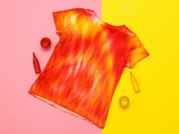 Camiseta no estilo tie dye, tinta e pincel em uma superfície amarela e laranja