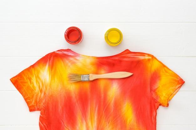 Camiseta pintada no estilo tie dye e potes com vermelho e amarelo em uma mesa branca