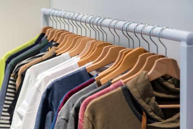 Camisetas de grife em exposição em uma loja de varejo. camisas de cores e texturas diferentes penduradas em um cabide