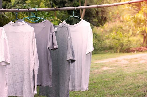 Camisetas penduradas na barra de madeira para secar após a limpeza de roupas no jardim ao ar livre na casa de campo
