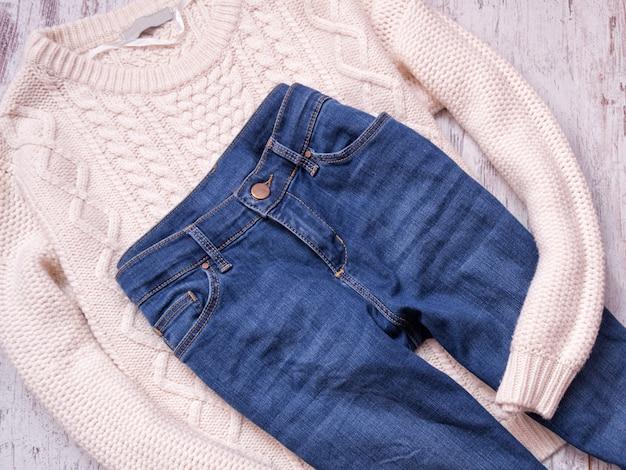 Camisola branca e calça jeans em um fundo de madeira, vista superior
