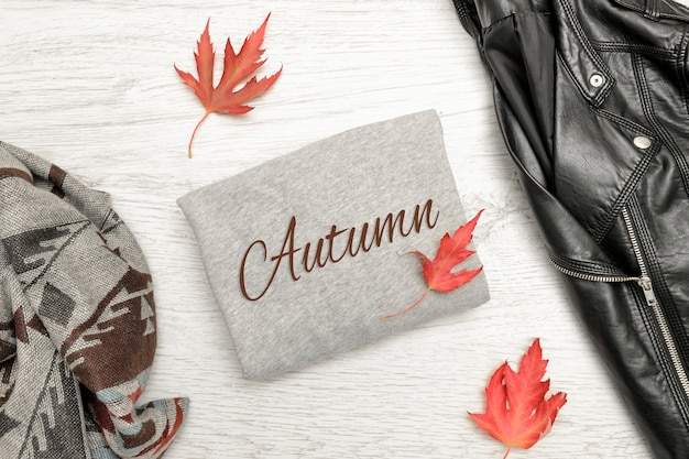 Camisola cinza com a inscrição outono, jaqueta preta, cachecol e folhas de outono. elegante