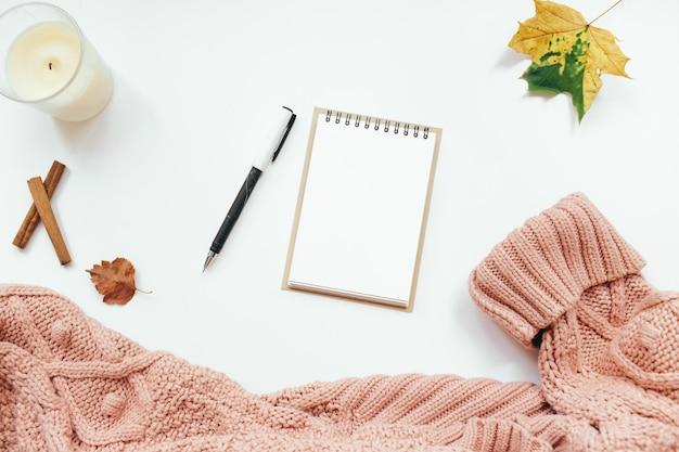 Camisola de malha, caderno, folhas de outono, paus de canela, vela em fundo branco. composição de outono. camada plana, vista superior, espaço de cópia