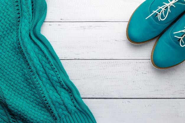 Camisola de malha de cor aqua e sapatos oxford de camurça verde sobre fundo de madeira.