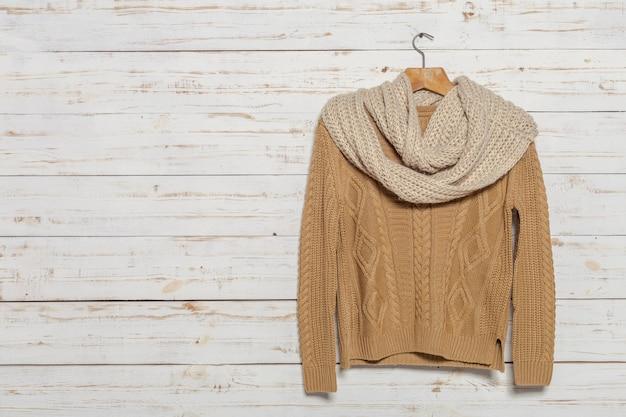 Camisola de malha no rack de roupas de madeira