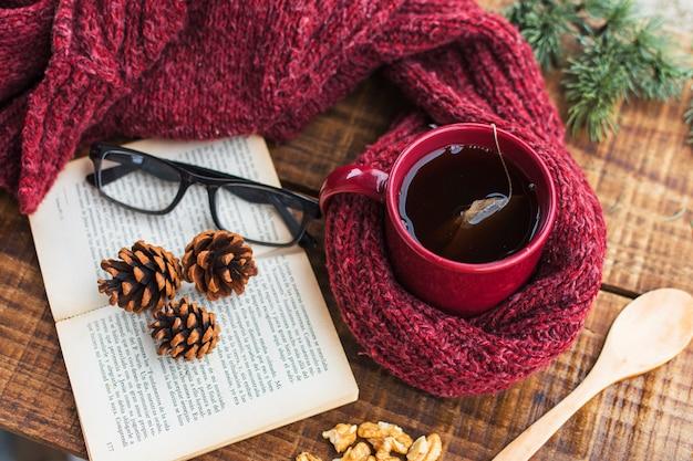 Camisola e chá perto de livro e óculos