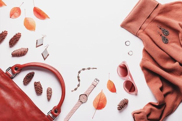 Camisola marrom mulher com bolsa de couro, acessórios de moda e folhas de outono Foto Premium