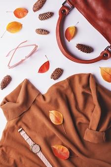 Camisola marrom mulher com bolsa de couro, acessórios de moda e folhas de outono
