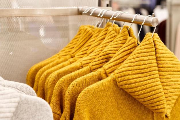 Camisolas de malha de lã cor amarela moda ceylon pendurado em cabides na loja, close-up