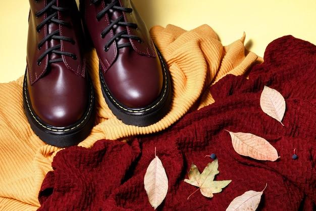 Camisolas de outono e botas em um fundo amarelo. clima de outono