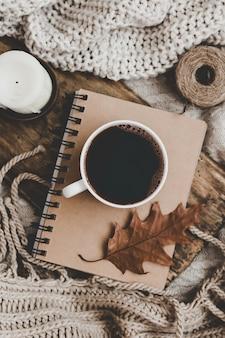 Camisolas e xícara de chá com caderno, vela e roupas de tricô