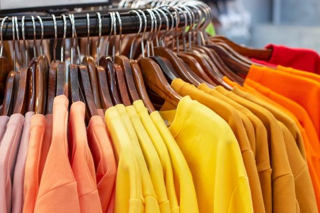 Camisolas multicoloridas femininas em cabides de madeira