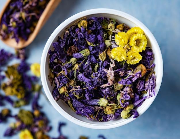Camomila e chá de ervas aromáticas secas de lavanda soltas perto de copo branco na macro de mesa de madeira azul