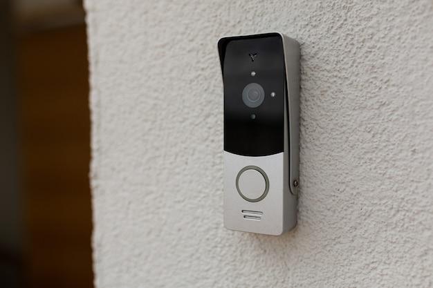 Campainha na parede da casa com câmera de vigilância