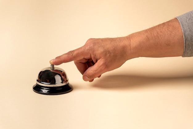 Campainha prateada do hotel, com mão humana tocando-a com fundo bege