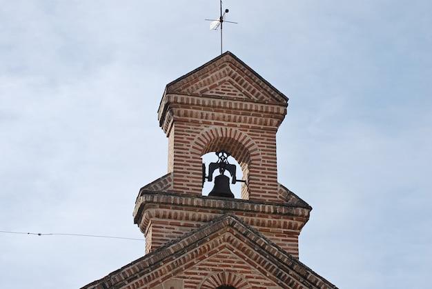 Campanário da capela com sino, cruz e vane