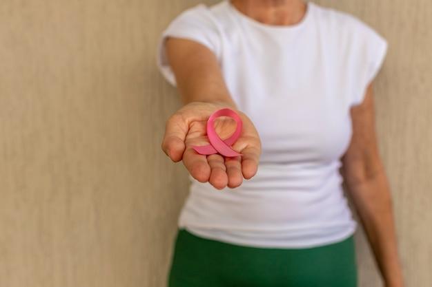 Campanha de prevenção do câncer de mama outubro rosa saúde da mulher mulher com laço rosa na frente