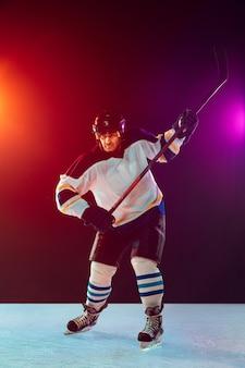 Campeão. jogador de hóquei masculino na quadra de gelo e fundo colorido de néon escuro com lanternas. desportista em equipamento, treino de capacete. conceito de esporte, estilo de vida saudável, movimento, bem-estar, ação.