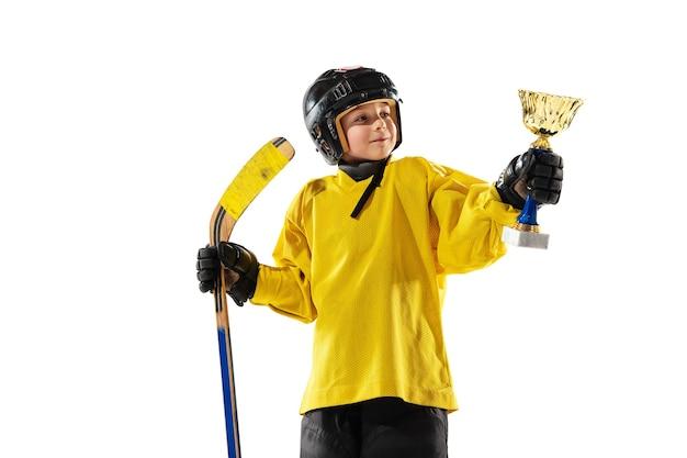 Campeão. pequeno jogador de hóquei com o taco na quadra de gelo e parede branca. desportista usando equipamento e treinamento de capacete. conceito de esporte, estilo de vida saudável, movimento, movimento, ação.