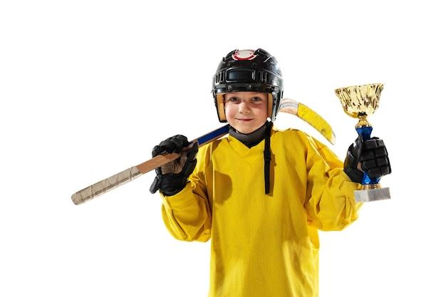 Campeão. pequeno jogador de hóquei com o taco na quadra de gelo e parede branca do estúdio
