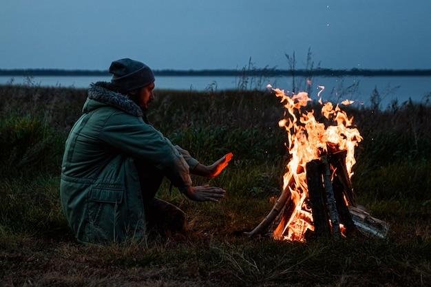 Camping homem sentado perto do fogo à noite contra o céu. viagens, turismo, camping.