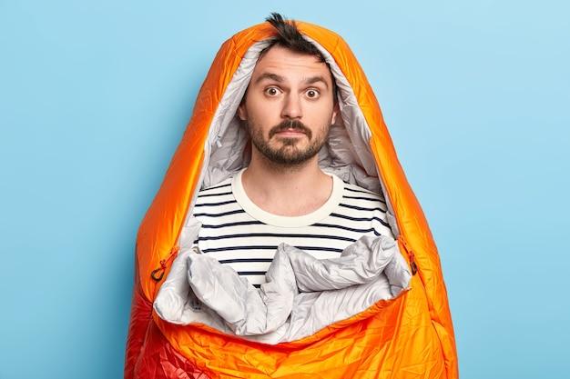 Campista barbudo surpreso posa em um saco de dormir, usa um macacão listrado, passa o fim de semana ativamente, posa sobre uma parede azul, faz expedição perto de montanhas rochosas