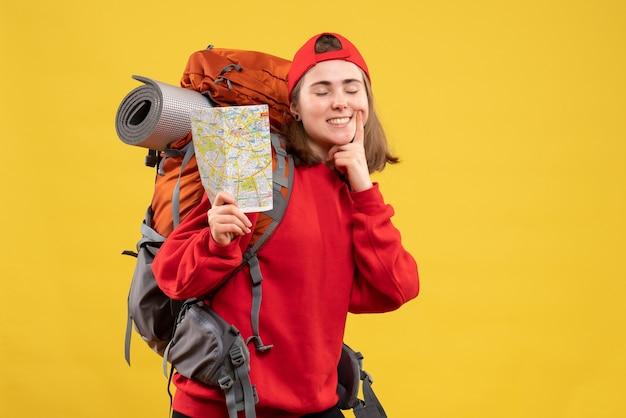 Campista feminina sorridente de vista frontal com mochila vermelha segurando mapa