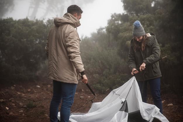 Campistas de tiro médio, montando uma barraca
