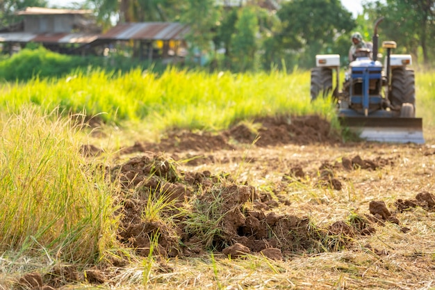Campo agrícola e trator trabalhando para a época de semeadura