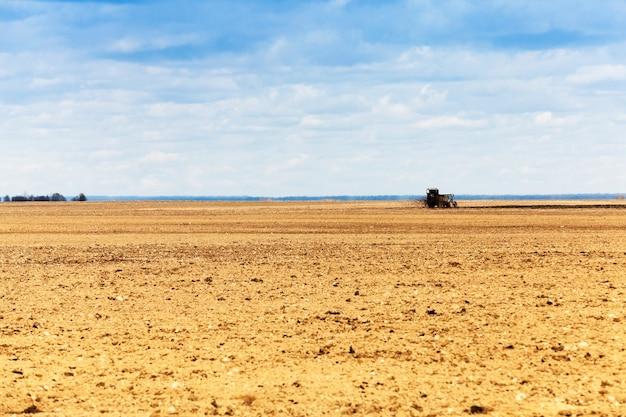 Campo agrícola em que o trator circula e fertiliza o solo.