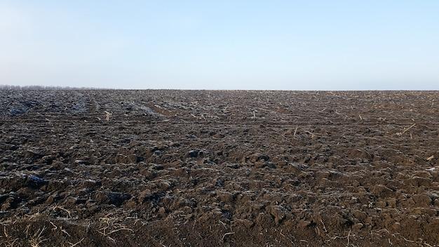 Campo agrícola lavrado por tratores sob o céu azul. o campo foi arado, as colheitas foram semeadas. feche acima da textura do solo. cena rural. agricultura e indústria alimentar. terra arável de chernozem.