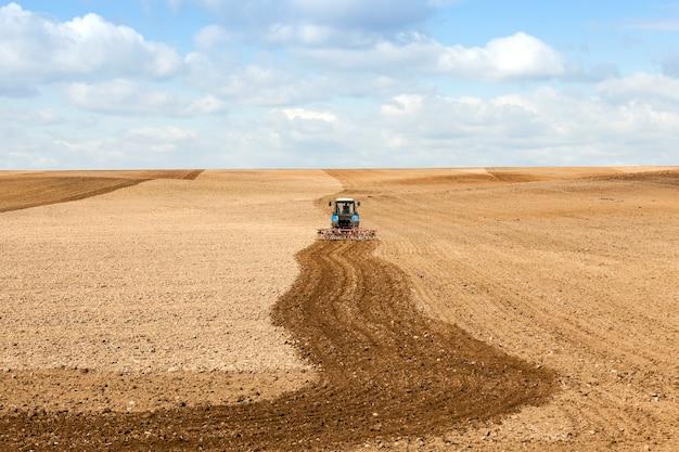 Campo agrícola, que ara o trator, preparação do terreno na primavera, céu