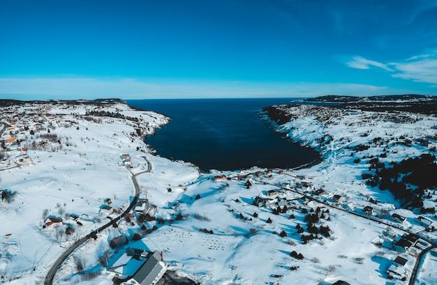 Campo coberto de neve perto do corpo de água durante o dia
