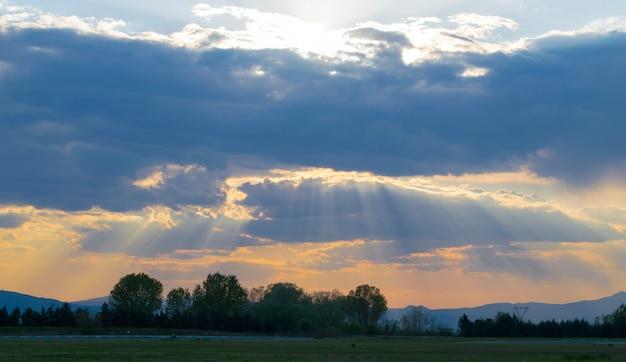 Campo coberto de vegetação sob um céu nublado durante um belo pôr do sol ao anoitecer