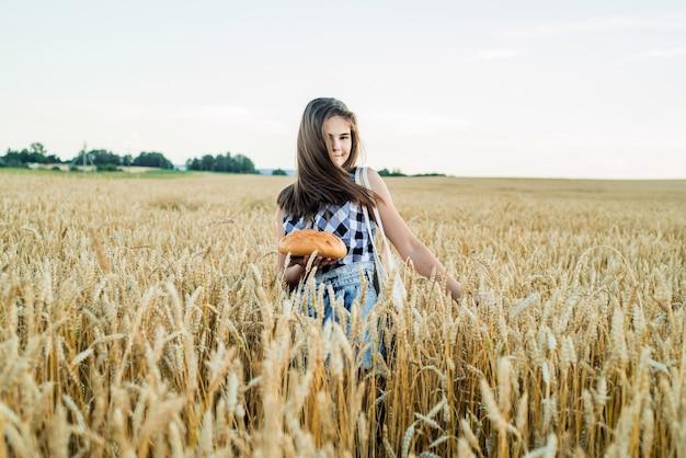 Campo com espigas de milho, uma colheita de bread.teenager girl segurando o pão redondo. pão no fundo das espigas de trigo. mãos segurando um pão grande. produtos de panificação em um campo de trigo