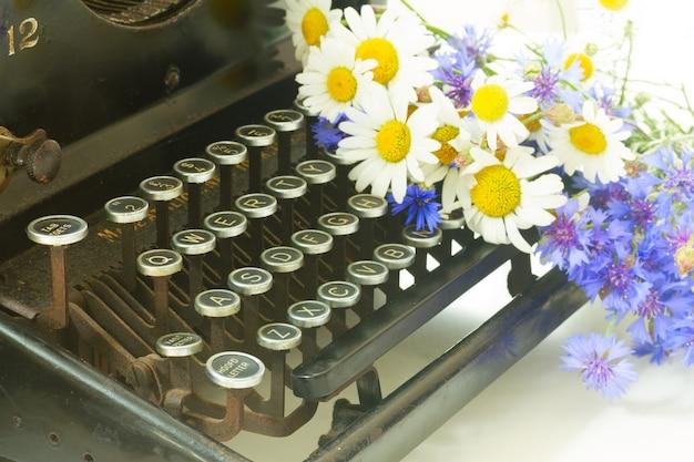 Campo dasies frescas, flores de milho e máquina de escrever vintage preta de perto