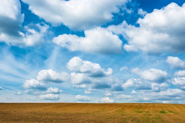 Campo de agricultura e céu azul com nuvens.