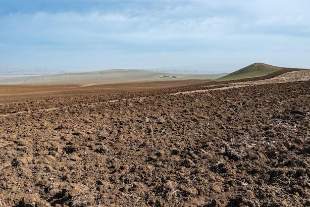 Campo de fazenda arado no vale da montanha
