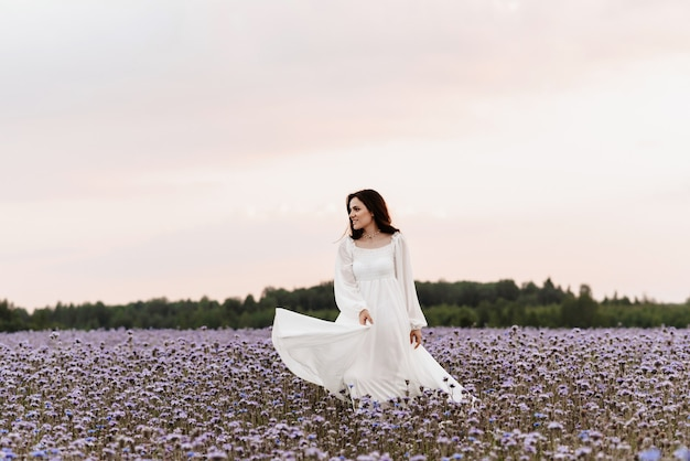 Campo de florescência de provence. a garota está feliz e ri correndo pelo campo florido.