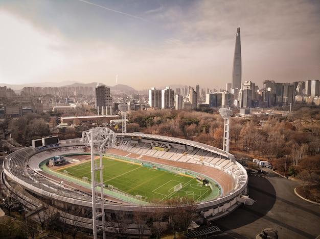 Campo de futebol com lotte world tower em fundo