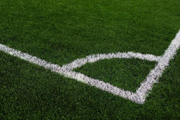 Campo de futebol de grama artificial com canto de linha branca no campo de futebol verde.
