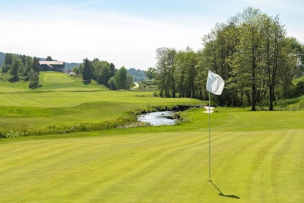 Campo de golfe. buraco com uma bandeira branca em um dia ensolarado