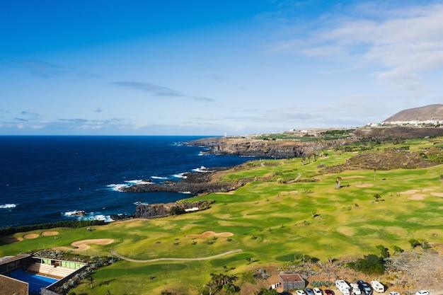 Campo de golfe perto do oceano atlântico em tenerife, espanha, campo de golfe verde, campo de ténis na natureza de tenerife