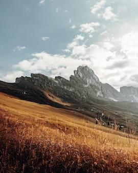Campo de grama marrom perto de montanhas sob nuvens brancas durante o dia