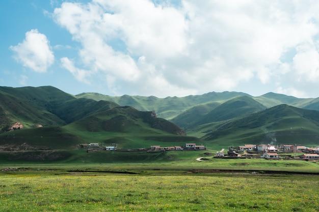 Campo de grama verde e montanha sob nuvens brancas e céu azul durante o dia
