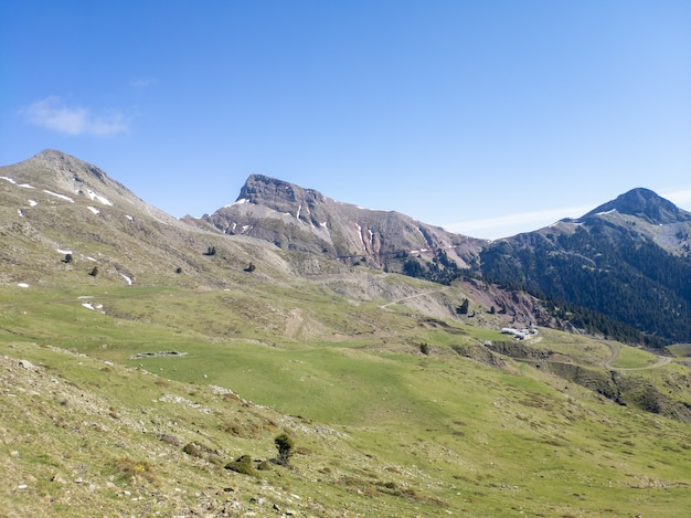 Campo de grama verde perto da montanha sob o céu azul durante o dia (2)