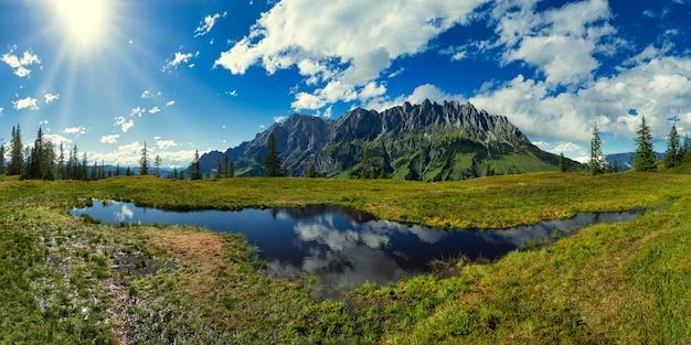 Campo de grama verde perto do lago, sob céu azul e nuvens brancas durante o dia