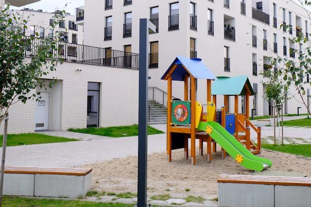 Campo de jogos colorido das crianças em um pátio acolhedor do distrito residencial moderno.