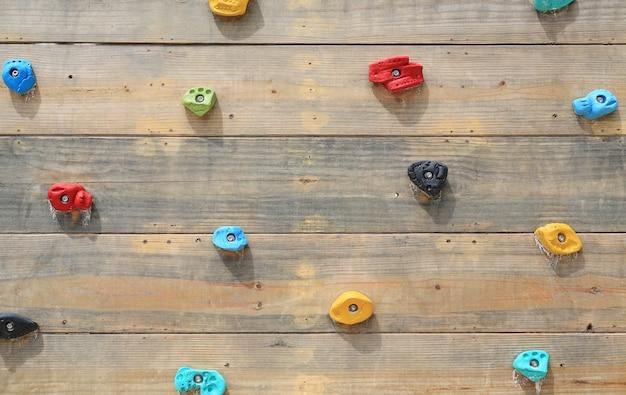 Campo de jogos da escalada de rocha na parede de madeira.