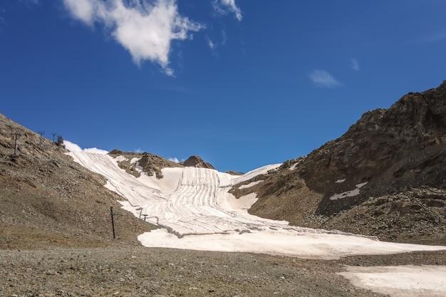Campo de neve de verão nos alpes suíços coberto por um pano que o protege do calor